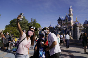 A family takes a photo in front of Sleeping Beauty's Castle at Disneyland in Anaheim, California, on Friday.