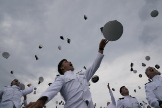 Graduates of the US Naval Academy class of 2021 throw their hats after Vice-President Kamala Harris delivered their commencement speech on the day the White House delivered the 2022 fiscal budget.