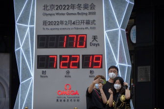 People take selfies in front of a display showing a countdown clock to the 2022 Winter Olympics in Beijing.