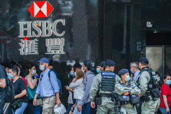 Riot police stand guard in front of an HSBC branch in Hong Kong's Central district on Friday.
