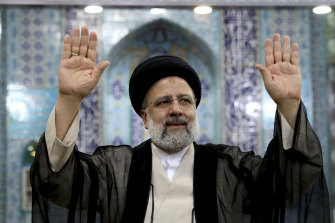 Ebrahim Raisi, Iran's new President, waves to media after casting his ballot in Tehran on Friday.
