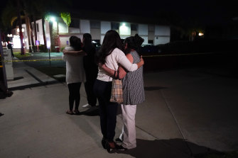 People comfort each other as they stand near the building where four people, including a child, were killed in Orange, California.