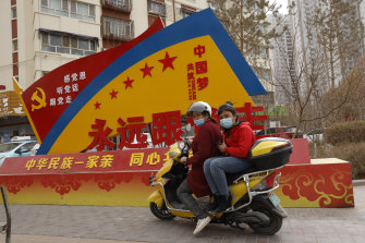 "A sign displays slogans ""China's ethnicities, one family"" and ""Forever follow the party"" in Aksu, Xinjiang."