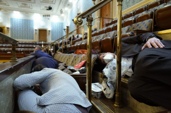 People shelter in the gallery as protesters try to break into the House Chamber on January 6.