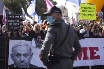 A police officer stands guard in front of protesters as Prime Minister Benjamin Netanyahu's motorcade arrives at his corruption trial hearing on Monday.