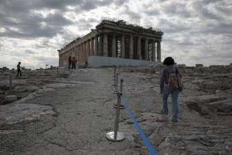 An employee of the Greek Culture Ministry walks alongside a belt separating visitors into sections at the archaeological site of the Acropolis, in Athens.