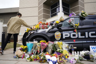 A man leaves a bouquet on a police car parked outside the Boulder Police Department following the shooting.
