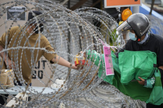 A resident, left, receives food from a delivery man through barbed wire at Segambut Dalam on the outskirts of Kuala Lumpur.