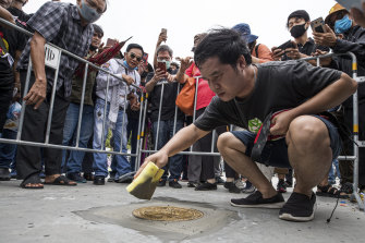 """A pro-democracy supporter fixes a plaque which declares """"This country belongs to the people"""" during a protest in Bangkok on Sunday."""