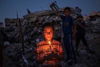 Palestinian children hold a candle and the Palestinian flag amid the ruins in Beit Lahiya in the Gaza Strip.