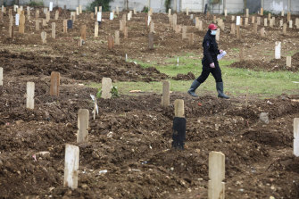 An employee walks among graves at the special section of Srengseng Sawah cemetery which was opened to accommodate the surge in deaths in Jakarta.