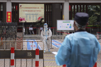 A student in full protective gear leaves after taking college entrance exams in a special quarantined exam station for students who had close contacts with recent coronavirus cases in Guangzhou, China, on Monday.
