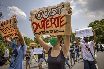 Protesters wearing masks hold up placards as they protest an anti-terror bill, President Rodrigo Duterte is trying to expedite. Rights groups warn the law contains draconian provisions that could be used to target his critics.