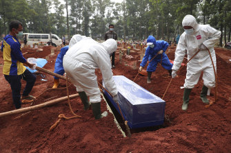 Workers in Indonesia lower a coffin of a COVID-19 victim into a grave.  The nation has recently been hit hard by the pandemic.