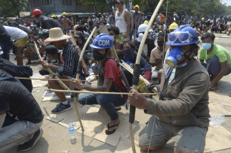 Anti-coup protesters prepare makeshift bow and arrows to confront police in Thaketa township Yangon, Myanmar, on Saturday, as more than 100 were killed by soldiers and police.