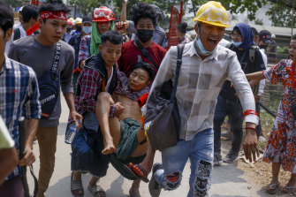 Anti-coup protesters carry an injured man following clashes with security in Yangon, Myanmar, on Sunday.