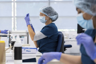 Pharmacists prepare the Pfizer vaccine at the Sydney Olympic Park mass vaccination clinic.