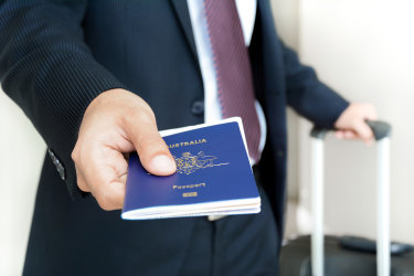 Businessman showing passport (of Australia) - business travel, check in and immigration concepts iStock image for Traveller. Re-use permitted. Australian passport