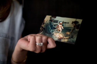Eve Wiley, who learned through DNA testing that her biological father was her mother's fertility doctor, holds a photo of her birth.