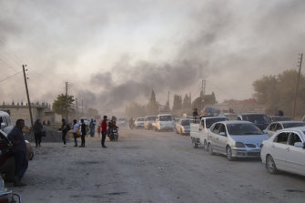 Syrians flee shelling by Turkish forces in Ras al Ain in north-east Syria.