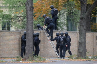 Police officers climb over a wall at the crime scene in Halle, Germany.