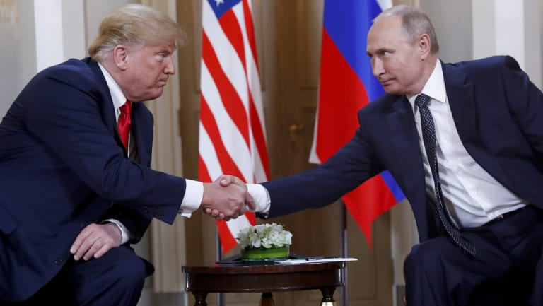 US President Donald Trump, left, and Russian President Vladimir Putin, right, shake hands at the beginning of a meeting at the Presidential Palace in Helsinki, Finland, on June 16.