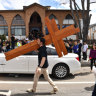 A man carrying crosses walks past Prime Minister Scott Morrison's car after Good Friday Easter services at St Charbel's Catholic Maronite Church at Punchbowl.