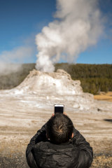 A visitor photographs Castle Geyser in Yellowstone National Park last month.