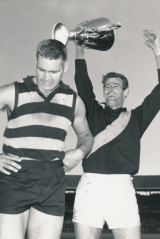 Richmond captain Fred Swift holds aloft the premiership cup, beside Geelong captain Polly Farmer.