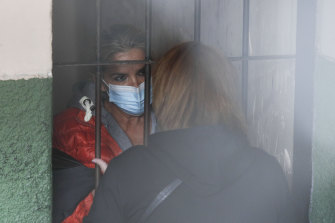 Standing behind bars, Bolivia's former interim President Jeanine Anez speaks to an unidentified woman at a police station jailhouse, in La Paz, Bolivia.