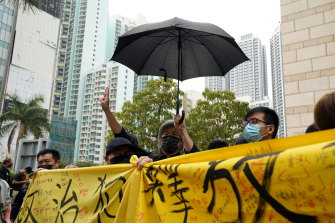 """Supporters of pro-democracy activists hold a banner reading """"release political prisoners"""" as they queue up outside West Kowloon Magistrates' Courts in Hong Kong on Monday."""