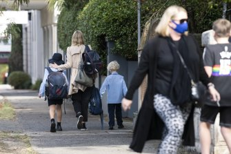 Parents collect their children from St Charles' Primary School at Waverley after a year 3 student tested positive to COVID-19.