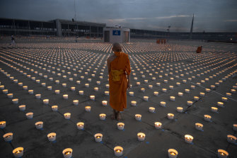 Buddhist novice monks light 180,000 candles during Vesak Day celebration at Wat Phra Dhammakaya temple on the outskirts of Bankok on Wednesday. Devotees had to attend the ceremony via Zoom this year because of COVID-19.