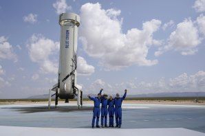 Jeff Bezos, second from left, in front of the rocket that landed safely after their launch from the spaceport near Van Horn, Texas, in July 20.
