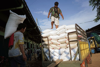 A worker carries a sack of rice while loading a truck at a grain market in Jakarta, Indonesia.
