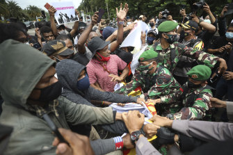 West Papuan activists scuffle with Indonesian soldiers and police officers trying to confiscate their banner during a rally calling for the remote region's independence in Jakarta in December.