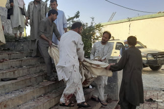 People carry a victim from a mosque following a bombing in Kunduz province, northern Afghanistan.