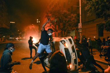 Demonstrators vandalise a car as they protest the death of George Floyd near the White House on Sunday night.