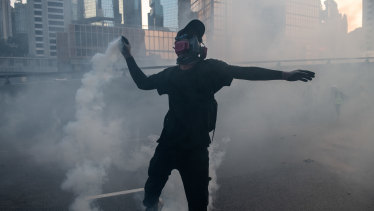 A pro-democracy protester throws a police teargas cartridge back at police officers.