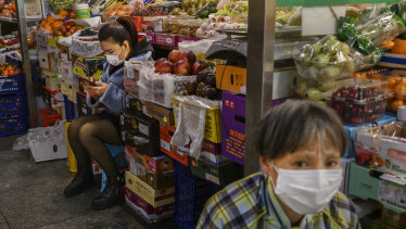 Fruit vendors wear protective masks as they wait for customers at a local market in Beijing, China.