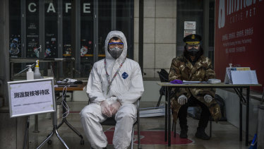 A guard waits to check temperatures and register people entering a building in Beijing. China has put huge effort into containing COVID-19.