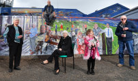 Artist Simon White, sitting on fence, with his mural on the LakeView Bar and Bistro  in Loch Sport, depicting locals Noeleen Brown, left, Dulcie Benham, Renee Meers, 6, holding the publican's dog Pushka, and Donny Morton.
