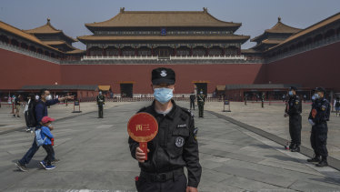 A Chinese guard wears a protective mask as he stands at the entrance to Beijing's Forbidden City.