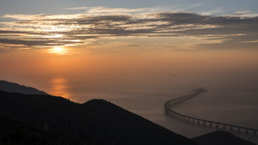 The eastern artificial island and the Hong Kong Link Road section of the Hong Kong-Zhuhai-Macau Bridge stand offshore at sunset in Hong Kong, China.