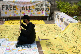 A supporter of pro-democracy activists holds a sign outside West Kowloon Magistrates' Courts where others queue up for a court hearing over charges  of subversion on Monday.