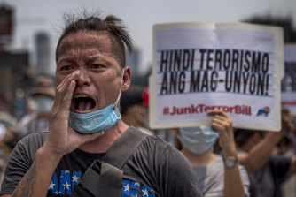 Protesters wearing masks hold up placards as they protest the anti-terror bill in Quezon city, Philippines, on Wednesday.