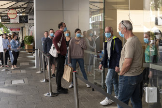 Customers wait outside the Perth Apple Store wearing masks.