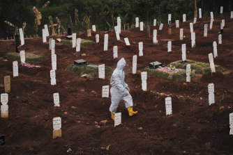 A municipal cemetery worker walks through  a special cemetery for suspected  Covid-19 victims in Jakarta, Indonesia.