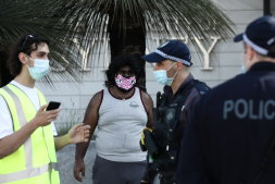 Police question a protester at Sydney University during a demonstartion over cutbacks.