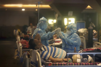 Health workers attend to COVID-19 patients at a makeshift hospital in New Delhi on Friday.